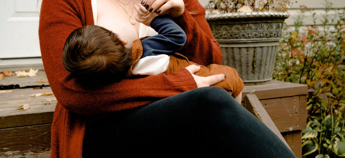 photo of woman breastfeeding her child