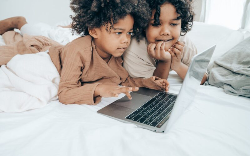 ethnic brothers using laptop on bed