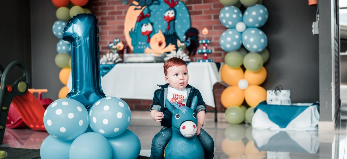 photo of child sitting on toy near balloons
